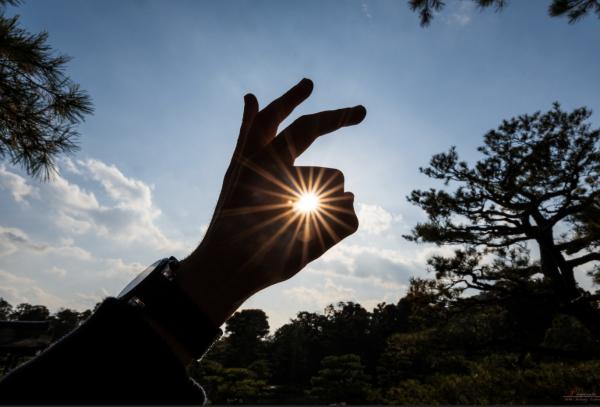 太陽を指で囲んでいる画像